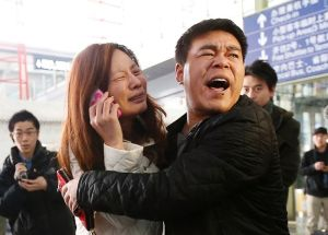 A relative (woman in white) of a passenger onboard Malaysia Airlines flight MH370 cries as she talks on her mobile phone at the Beijing Capital ...
